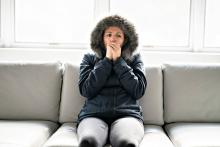 woman wearing winter jacket at home inside