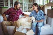 new homeowners inside house with dog on couch surrounded by boxes