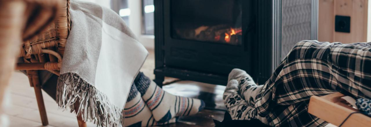 Couple with black cat relaxing by woodstove