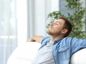 Man relaxing on a couch because he is cool durign the hot summer months thanks to The Fifth Fuel in Manassas Virginia
