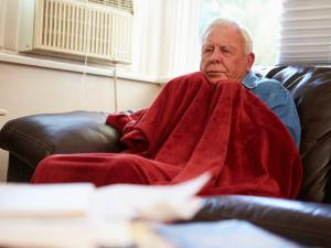 cold man under a blanket at home