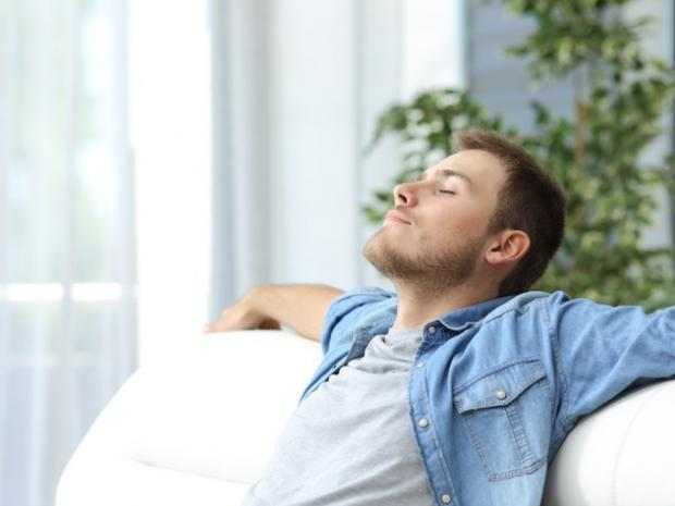 Man relaxing on a couch because he is cool