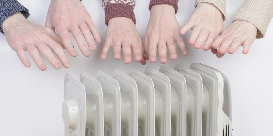 Hands reaching for a space heater because they are cold in the Manassas Virginia area